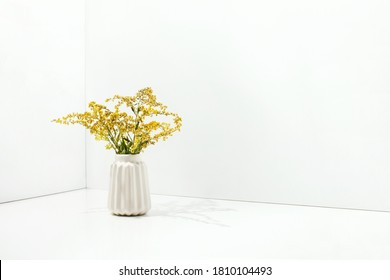 White simple vase with yellow flowers, front view, blank space for a text