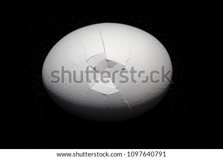 White single broken egg on bold black background. Macro horizontal composition in natural light.