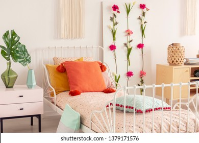 White single metal bed with colorful pillows and doted bedding in chic boho bedroom interior