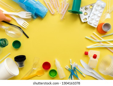White single-use plastic and other plastic items on a yellow background. The concept of choice without plastic or environmental problems.