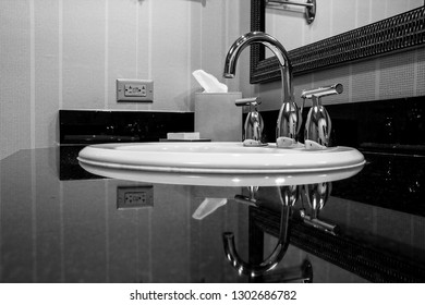 White sink with chrome taps for hot and cold water on black marble plate