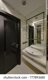 A white sink with a curbstone and a mirror and a black glossy door