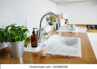 White sink with dishes ready to wash. Modern white kitchen scandinavian style, zero waste eco friendly home