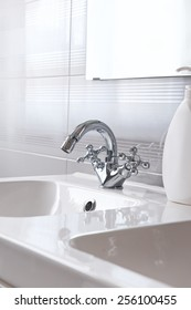 White sink with Steel faucet in a bathroom