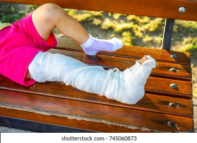 white skin kid with broken left leg sit on the brown wooden bench against dry yellow leaves and sunshine. tired child with broken leg in white gypsum rest on park bench.