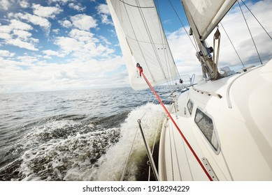White sloop rigged yacht sailing in an open sea on a clear day. A view from the deck to the bow. Cumulus clouds. Transportation, travel, cruise, sport, recreation, leisure activity, racing, regatta
