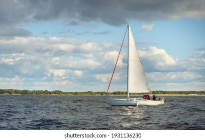 White sloop rigged yacht sailing in the Baltic sea at sunset. Dramatic sky after the storm, ornamental clouds. Transportation, travel, cruise, sport, recreation, leisure activity, racing, regatta