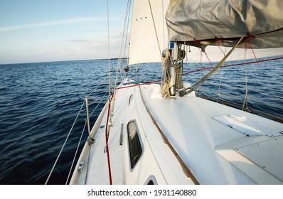Weiße Hangyacht, die bei Sonnenuntergang im Meer segelt. Himmel frei. Ein Blick vom Deck auf den Bogen, Mast, Segel. Verkehr, Reisen, Kreuzfahrten, Sport, Erholung, Freizeitaktivitäten, Rennen, Regatta