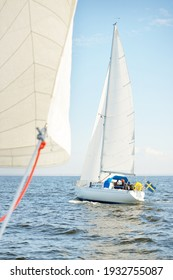 White sloop rigged yacht sailing in an open sea. Clear sky, cloudscape. A view from the sailboat. Transportation, travel, sport, recreation, leisure activity, racing, regatta. Panorama, copy space