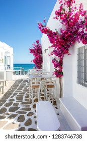 White small alley and houses with red bouganvillea flowers leading to the blue sea on the cyclades in Greece, Paros island, during summer time