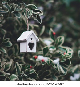 White small birdhouse with heart-shaped door hanging on a tree in winter