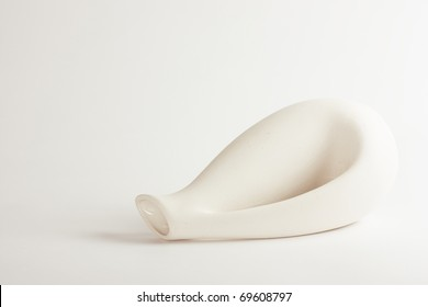 White small ceramic vase lies over white