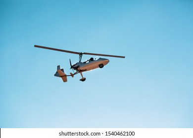 White small double gyroplane autogyro without a cabin against the blue sky. Air tours for tourists.