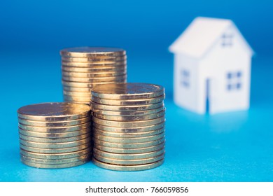 white small house and golden coins  on blue background, Real Estate concept  close up, selective focus
