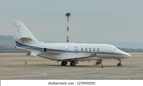 White small turbofan-powered business jet airplane on the apron of an airport. Fast modern aircraft for air transportation. Aviation technology. Travel and business concept.