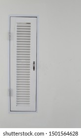 White small wooden louver door on white concrete wall.