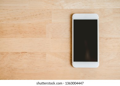 White smart phone with isolated screen on wooden desk. - Image