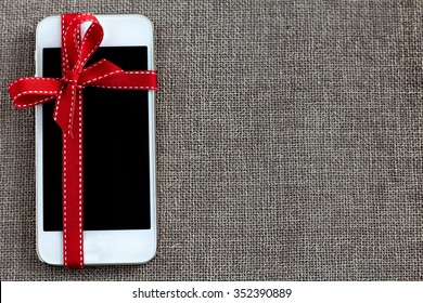 White smart phone with isolated screen on the contrast textile background