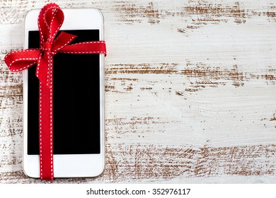 White smart phone with isolated screen on the wooden background