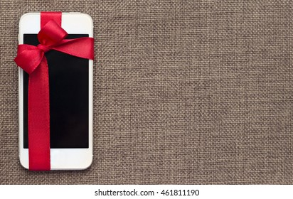 White smart phone with isolated screen on the contrast textile