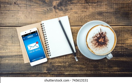 White Smart Phone with Notebook pencil and Cup of cappuccino on old wood table background in Cafe