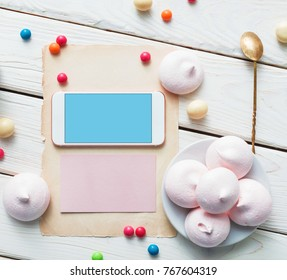 White smart phone on white wood with sweets and cookies. Top view with Clipping path.