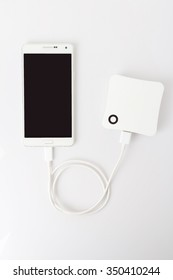 White smart phone with power bank on white background.