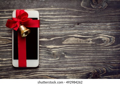 White smart phone with a red bow and golden bell on the wooden background