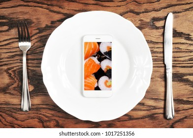 White smartphone with big white screen on the plate with silver knife and fork on the dark wooden background