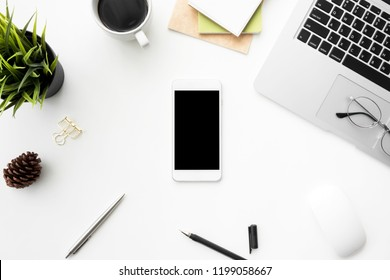 White smartphone with black blank screen is on top of white office desktable with laptop, gadgets and supplies. Top view with copy space, flat lay.