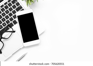 White smartphone with blank screen is on top of laptop on office desk with supplies. Top view with copy space, flat lay.
