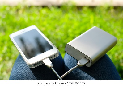 White smartphone charged by power bank on the knees on the background of green grass. Stay connected while traveling or camping.