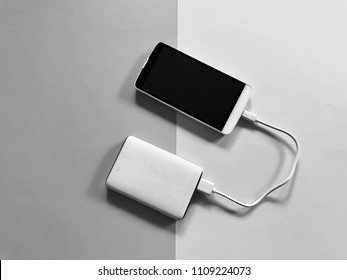A white smartphone charging with a white powerbank set on gray and white background. Top view with Copy space. Selective focus.
