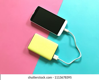 A white smartphone charging with a yellow powerbank on pastel pink and blue background. Charging smartphone on contrast color background. The concept of modern technology.Copy space. Selective focus.