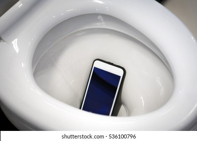 A white smartphone dropped into a toilet bowl
