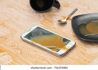 White Smartphone falls to the ground with broken and coffee spilled on wooden floor