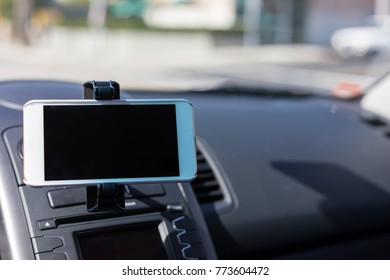 white smartphone in holder plugged in on dash showing empty blac
