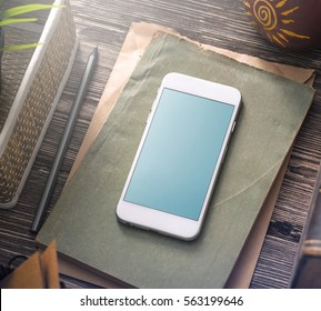 White smartphone mockup on the table with notes and old books. Clipping path