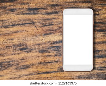 White smartphone on old wood table background.