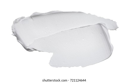 White smear of cosmetic cream isolated on white background. Creamy foundation texture isolated on white background. Smear of face cream isolated on white background. Texture of cream