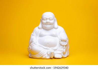 White smiling porcelain buddha statue sitting in a meditation position. Studio religious figure still life against a seamless yellow background.