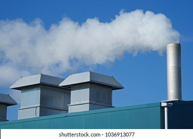 White smoke against blue sky from a cogeneration unit in modern greenhouse project