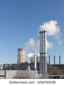 White smoke comes from a white chimney heat station pipe on a blue sky background. The environment. Greenhouse effect.