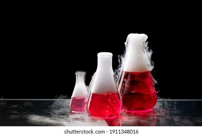 White smoke comes from a erlenmeyer flasks with red solution after addition of dry ice. Chemical reaction. Chemist demonstration experiment.