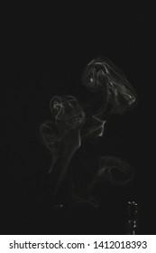 white smoke on black background. smoke waves from gas lighter - vintage retro look