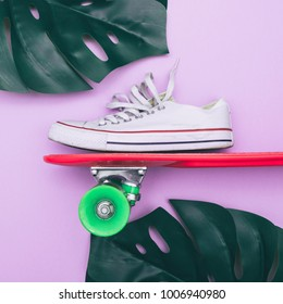 white sneaker on orange skateboard with palm leaf on purple background. fashion flat lay minimalism. creative concept