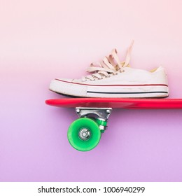 white sneaker on skateboard on purple and light pink gradient background. fashion flat lay minimalism. creative concept