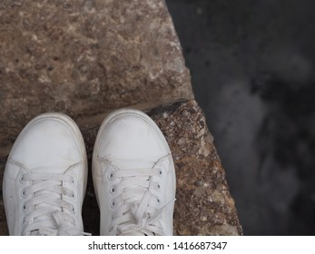 White sneaker on stone pavement.