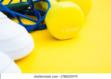 White sneakers, dumbbells and skipping rope on yellow background. Fitness and healthy lifestyle concept. Copy space
