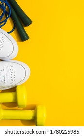 White sneakers, dumbbells and skipping rope on yellow background. Flat lay. Fitness and healthy lifestyle concept. Copy space